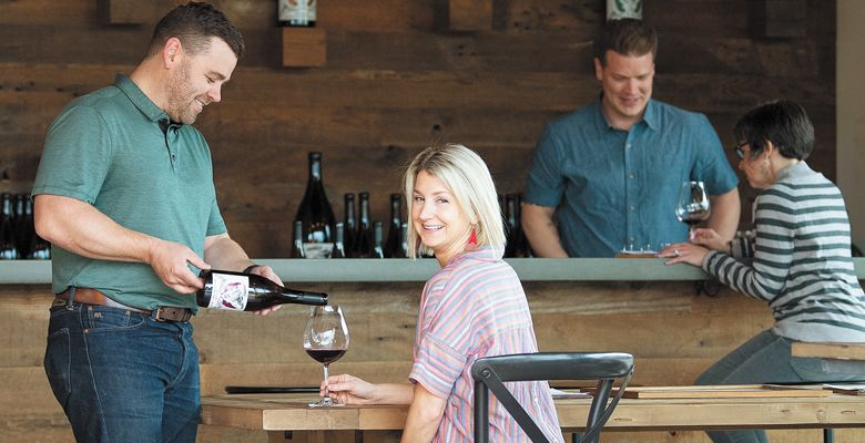 Purple Hands winemaker Cody Wright pour his wife, Marque, a glass of Pinot Noir at the Dundee tasting room on Highway 99W.  ##Photo by Andrea Johnson