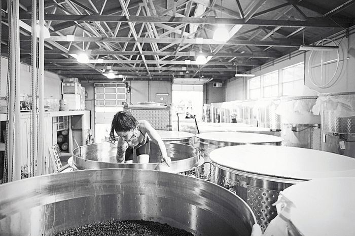 Sarah Cabot climbs into a tank while making Omero Pinot Noir.