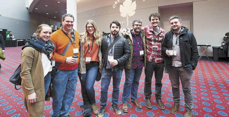 . Friends and colleagues meet in the lobby: (from left) Meagan Yount and Jeff Katz of Carlton Winemakers Studio; Kimberly Abrahams of Lingua Franca; Sean Vroomen of Adelsheim; Andrew Kirkland of Ruby Vineyard; James Braunagel of Lemelson; and Thomas Savre of Lingua Franca. ##Photos by Carolyn Wells-Kramer