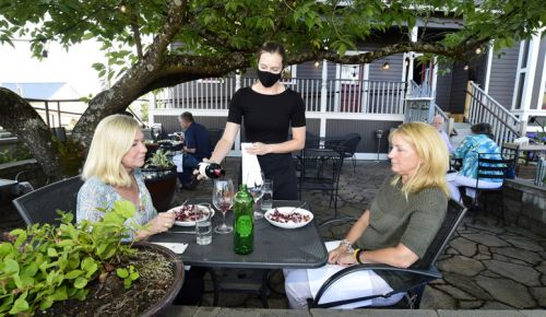 A masked server at Recipe in Newberg pours wine for guests on the elegant patio. ##Photo by Marcus Larson