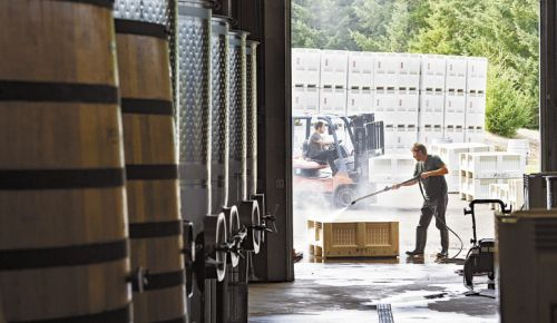 Workers at Penner-Ash Wine Cellars clean picking totes at the Newberg winery, which is now part of Jackson Family Wines. ##Photo by Andrea Johnson