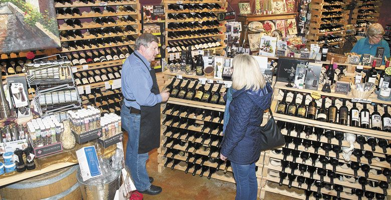 Mike Wallis, proprietor of The Cellar on 10th in Astoria, speaks with a customer at the wine shop. ##Photo by Andrea Johnson