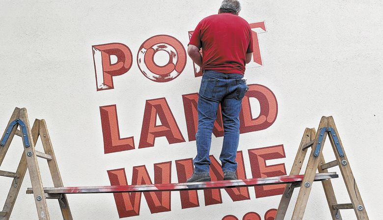 A contractor paints the modern-looking logo on Portland Wine Company's newly revitalized building in Southeast Portland. ##Photo provided