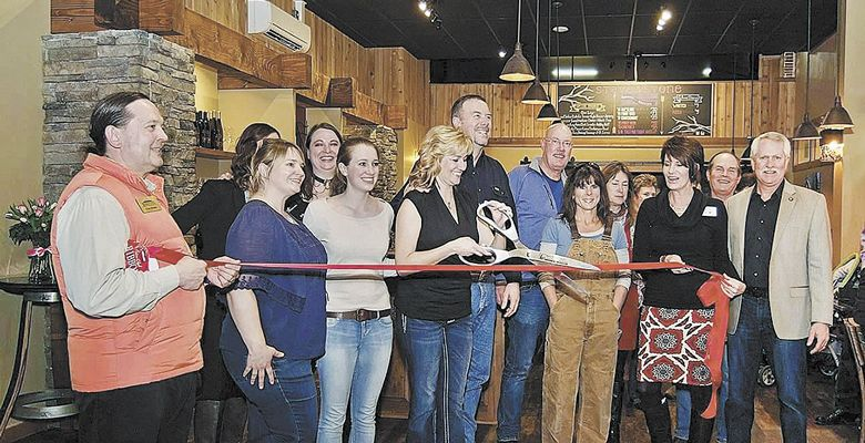 Jill House cuts the ribbon at the grand opening of Stave & Stone's tasting room in Hood River. Family and friends joined in on the celebration. ##Photo provided