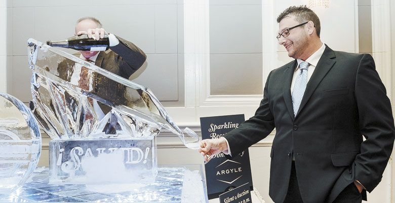A guest at the Saturday night ¡Salud! gala steadies his glass as it receives Arygle Brut  being poured via an impressive ice sculpture. ##Photo by Kathryn Elsesser
