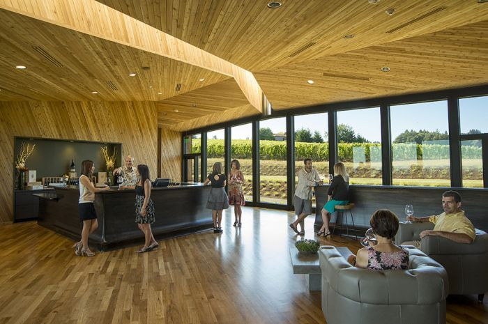 Inside the tasting room, guests mingle by the bar and in leather lounge chairs. Photo by Andrea Johnson.