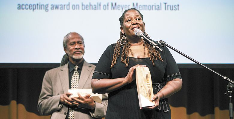 Michelle J. DePass accepts the Innovate Award on behalf of Meyer Memorial Trust. Standing behind her is Michael Alexander, recipient of the Inspire Award. ##Photo provided