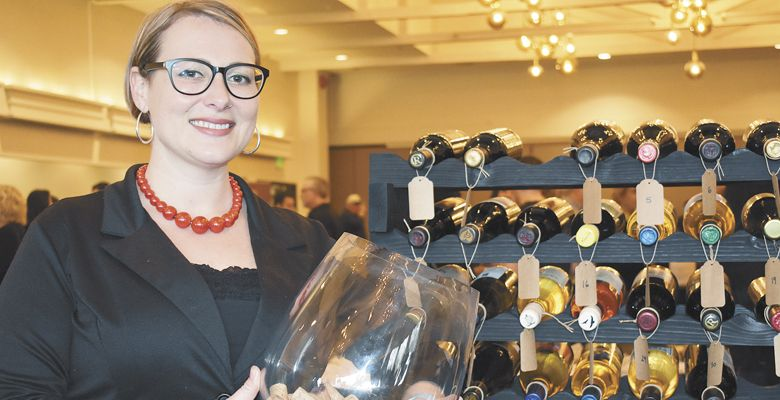 Event volunteer Brittney Schweizer-Wylie helps with the celebration's wine raffle. ##Photo by Maureen Battistella