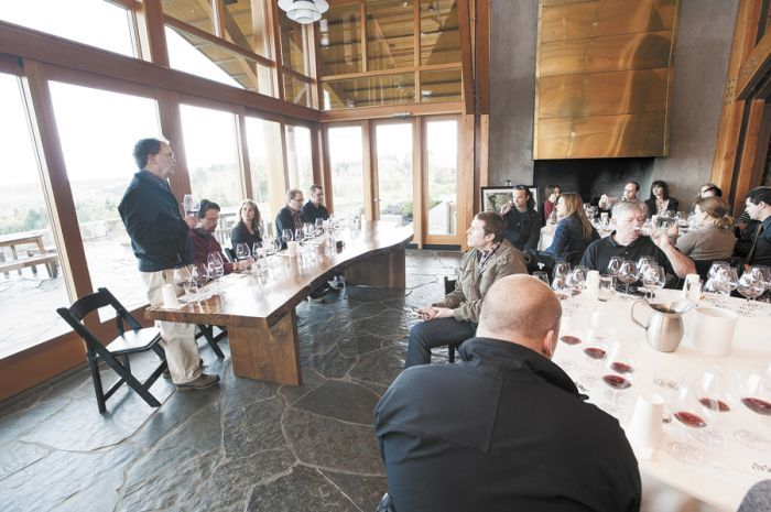 Dick Shea (standing) talks to guests gathered at a comparative tasting event called Tu Shea hosted at Penner-Ash Cellars outside Newberg. (From left) Scott Shull (Raptor Ridge), Lynn Penner-Ash, Stewart Boedecker and Bryan Weil (Alexana) join the discussion and offer their wines made with Shea fruit for the event.
