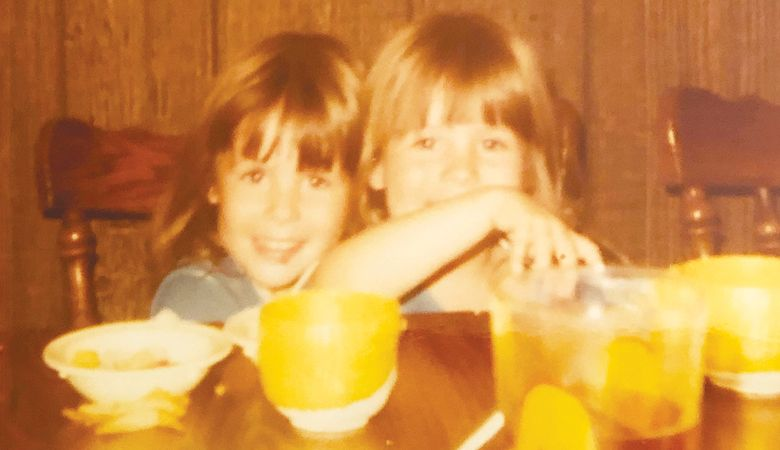 OWP editor Hilary Berg (right) with her twin sister, Jessica McHughes, at the  kitchen table of their youth.
