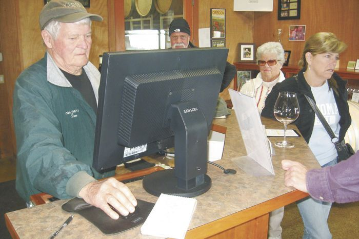 Vidon owner Don Hagge rings up a sale while visitors from New York, Florida and California sample his estate Pinots.