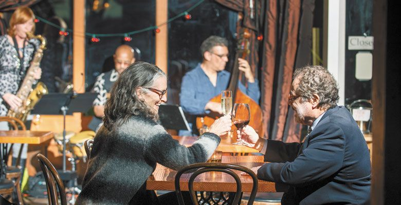 "A couple toasts the evening while enjoying the Portland-based ""new jazz"" trio. ##Photo by Kathryn Elsesser."