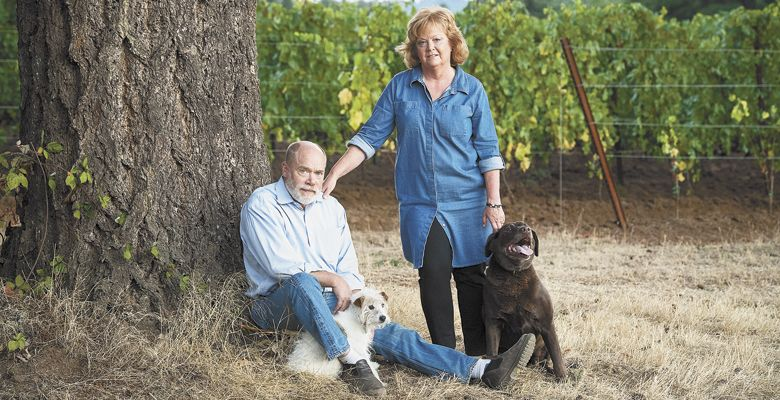 Celia and Ken Austin at Rain Dance Vineyards in the Chehalem Mountains count on the partnership of Emerson, a chocolate Lab, and Bella, a Jack Russell terrier, to manage the property. ##Photo by Andrea Johnson