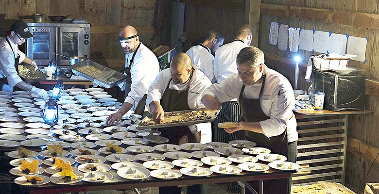 Hunt & Gather crew, led by co-owner/executive chef Andrew Biggs, assembles dishes in a barn at Bergström. Low-light conditions required staff to wear head lamps and light lanterns.