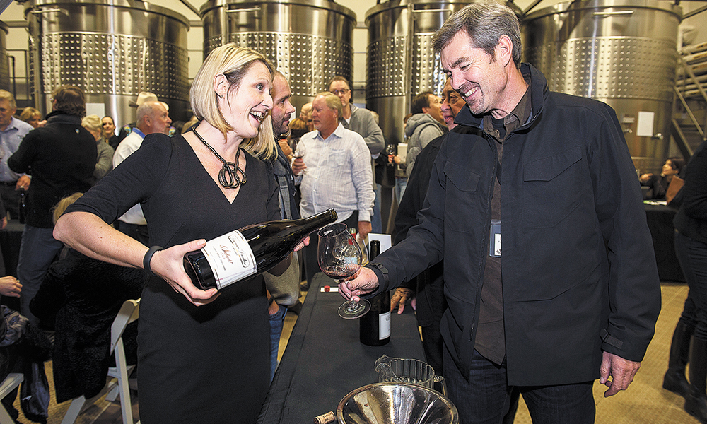 Ashley Bell of Domaine Drouhin Oregon pours a 2013 Pinot Noir for Ron Penner-Ash during the Big Board Auction held annually at Domaine Drouhin outside Dayton. ##Photo by Andrea Johnson