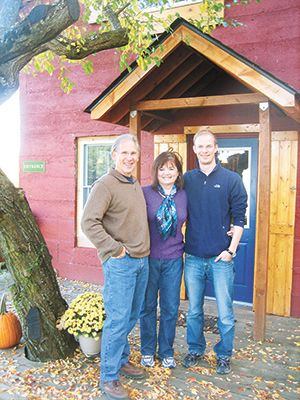 Owners Dick and Pat Ellis and their son, Teddy, stand in front Pebblestone Cellar's tasting room, a charming 1906 hand-poured concrete cottage. ##Photo provided.